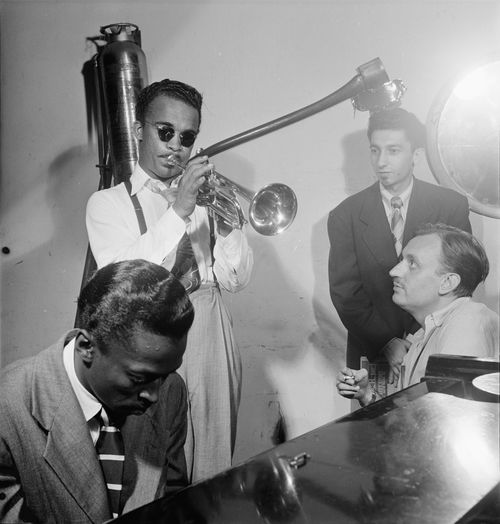 Miles-davis-on-piano-with-howard-mcghee-trumpet-joe-albany-pianist-standing-and-brick-fleagle-guitarist-smoking-september-1947